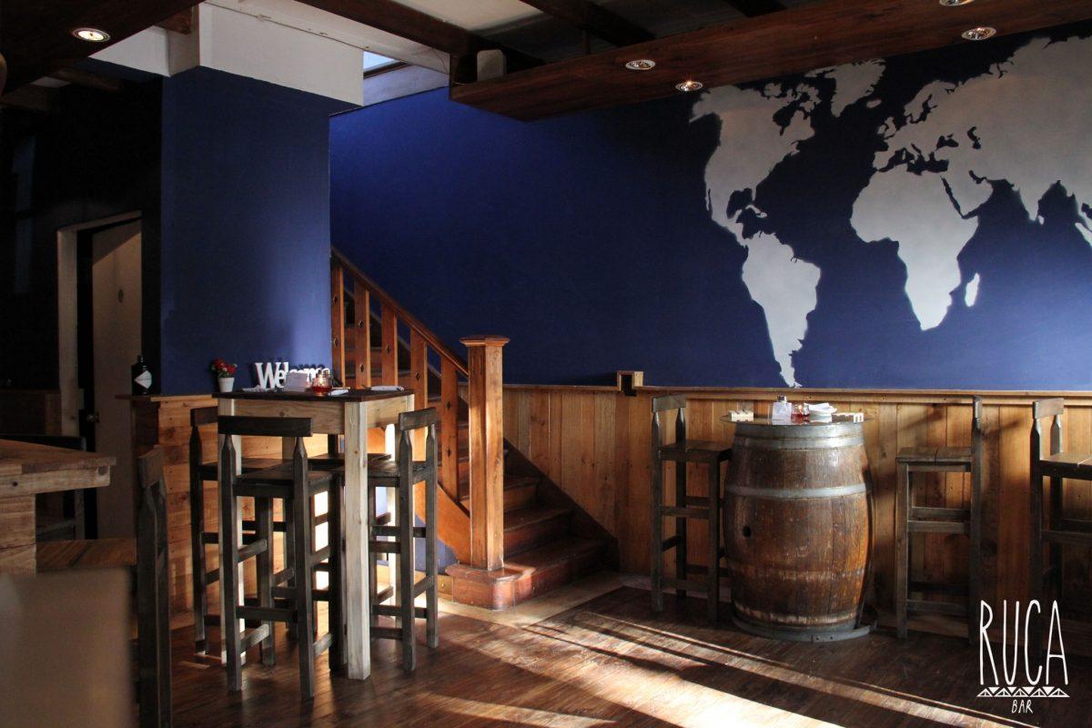 Vista del interior de Ruca Bar con sillas y mesas de madera y barriles.